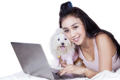 Lovely woman with laptop and dog on bed. Picture of pretty young woman smiling at the camera while using notebook on bed with her dog Royalty Free Stock Photos