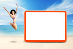 Lovely woman leaps at coast near the board Stock Image
