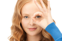Lovely woman looking through hole from fingers Stock Image