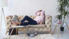 Lovely woman lying on cozy sofa relaxing after work stock video footage