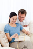 Lovely woman opening a present from her boyfriend Stock Image
