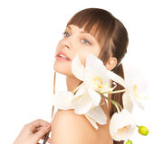Lovely woman with orchid flower Stock Image