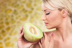 Lovely woman with perfect tan. Young lovely woman with complexion holding cantaloupe royalty free stock photos