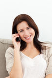Lovely woman on the phone sitting on the sofa Royalty Free Stock Image