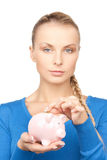 Lovely woman with piggy bank and money Stock Photo