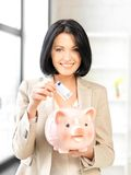 Lovely woman with piggy bank and money Royalty Free Stock Photography