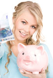 Lovely woman with piggy bank and money Stock Photography