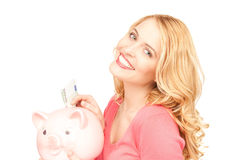 Lovely woman with piggy bank and money Royalty Free Stock Photo