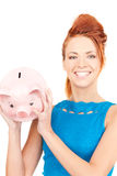 Lovely woman with piggy bank Stock Images