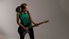 Lovely woman plays on guitar and listens to music stock footage