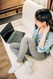 Bbeautiful woman using laptop computer at home on sofa. Lovely woman with pleasant appearance sits on comfortable sofa with legs crossed focused in laptop royalty free stock photography