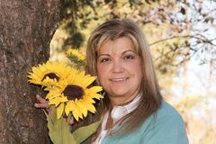 Lovely woman poses holding flowers next to tree. Woman poses near a tree holding holding sunflowers Royalty Free Stock Photos