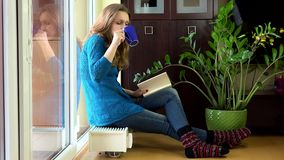 Lovely woman read book and drink coffee sitting on warm radiator. stock video