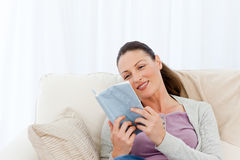 Lovely woman reading a romance sitting on the sofa Royalty Free Stock Photography