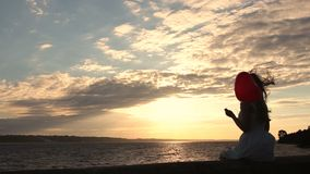 Lovely woman with red balloon on seaside at sunset stock footage