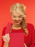 Lovely woman in red dress with opened gift box Royalty Free Stock Image
