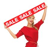 Lovely woman in red dress with sale sign Royalty Free Stock Photography