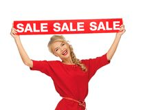 Lovely woman in red dress with sale sign Stock Photography