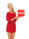 Lovely woman in red dress with sale sign Royalty Free Stock Photos