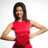 Lovely woman with red heart shaped gift box. Happiness, valentines day and love concept. Lovely elegant woman in red dress, girl mixed race holding red heart Royalty Free Stock Photography