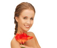 Lovely woman with red lily flower Stock Images