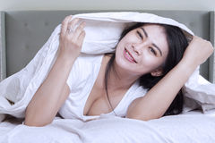 Lovely woman relaxing in bedroom and smiling Stock Photos