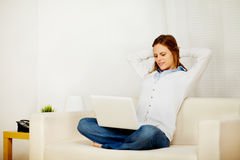 Lovely woman resting on sofa with a laptop Royalty Free Stock Images