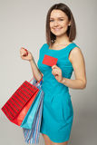 Lovely woman with shopping bags showing empty paper card, over gray background Royalty Free Stock Photos