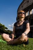 Lovely woman sitting on grass against Colosseum Royalty Free Stock Image