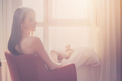 Lovely woman sitting and looking through a window admiring sunrise or sunset. Royalty Free Stock Photography