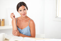 Lovely woman sitting while studying books Royalty Free Stock Photos