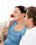 Lovely woman smelling a rose sitting on the sofa Royalty Free Stock Image