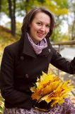 Lovely woman smiling with autumn leaves Stock Photos