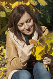 Lovely woman smiling with autumn leaves Stock Photo