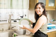 Beautiful woman holding plate and wipes it with towel. Lovely woman standing in kitchen and wiping dry plate with help of white cloth Royalty Free Stock Photo