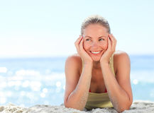 Lovely woman sunbathing at the beach. Lovely young woman sunbathing at the beach Royalty Free Stock Image