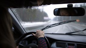 Lovely woman travelling by car on winter road. Pretty young woman driving car on the freeway admiring the beautiful landscape with snow and enjoying the stock video footage