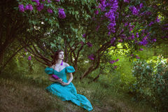 Lovely woman under a bush of lilac. royalty free stock photography