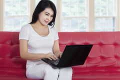 Lovely woman using laptop on sofa Royalty Free Stock Photos