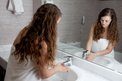 Lovely woman washing hand in bathroom. Dressed in towel beautiful woman washing hand at modern bathroom stock photos