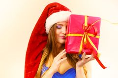 Woman in santa claus hat holds gift box. Christmas time. Lovely woman wearing santa claus hat holding big red christmas present, hiding her face behind gift Stock Image