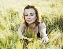 Lovely woman in the wheat cobs by sunset, natural beauty. Lovely caucasian woman in the wheat cobs by sunset. Natural beauty royalty free stock image