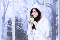 Lovely woman in winter coat drinks coffee Royalty Free Stock Images