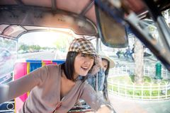 Lovely woman is driving auto rickshaw on the road so fast and feels happy, fun that makes her pretty friend gets scared and worry stock photo