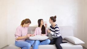 Cute girl friends collect girlfriend on date and help look beautiful, sit on couch in bright room in evening. stock footage