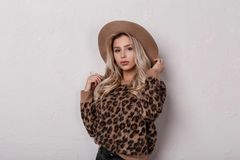 Lovely wonderful young woman with beautiful eyes with lips in an elegant beige hat in leather pants. In a vintage leopard sweater posing in the studio on white royalty free stock images