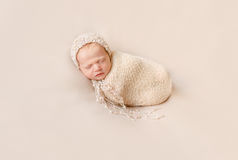 Lovely wrapped baby in hat sleeping on a beige blanket Stock Images