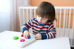 Lovely 2 years boy playing shape sorter. At home royalty free stock images