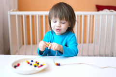 Lovely 2 years boy plays with beads of various colours Stock Photography