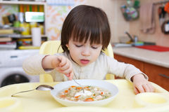 Lovely 2 years child eats cabbage soup. Healthy nutrition Stock Photos